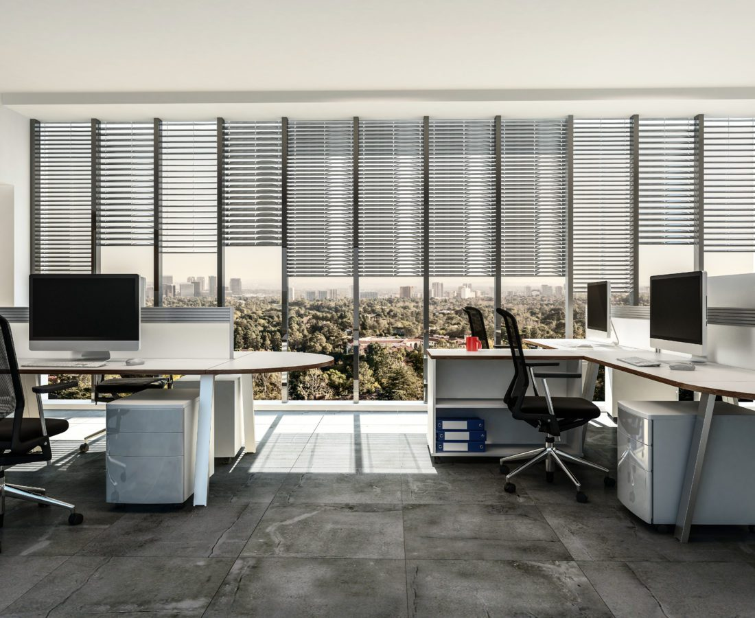 Modern business office with multiple workstations around table style desks with cabinets, tiled grey floor and large windows with blinds. 3d render