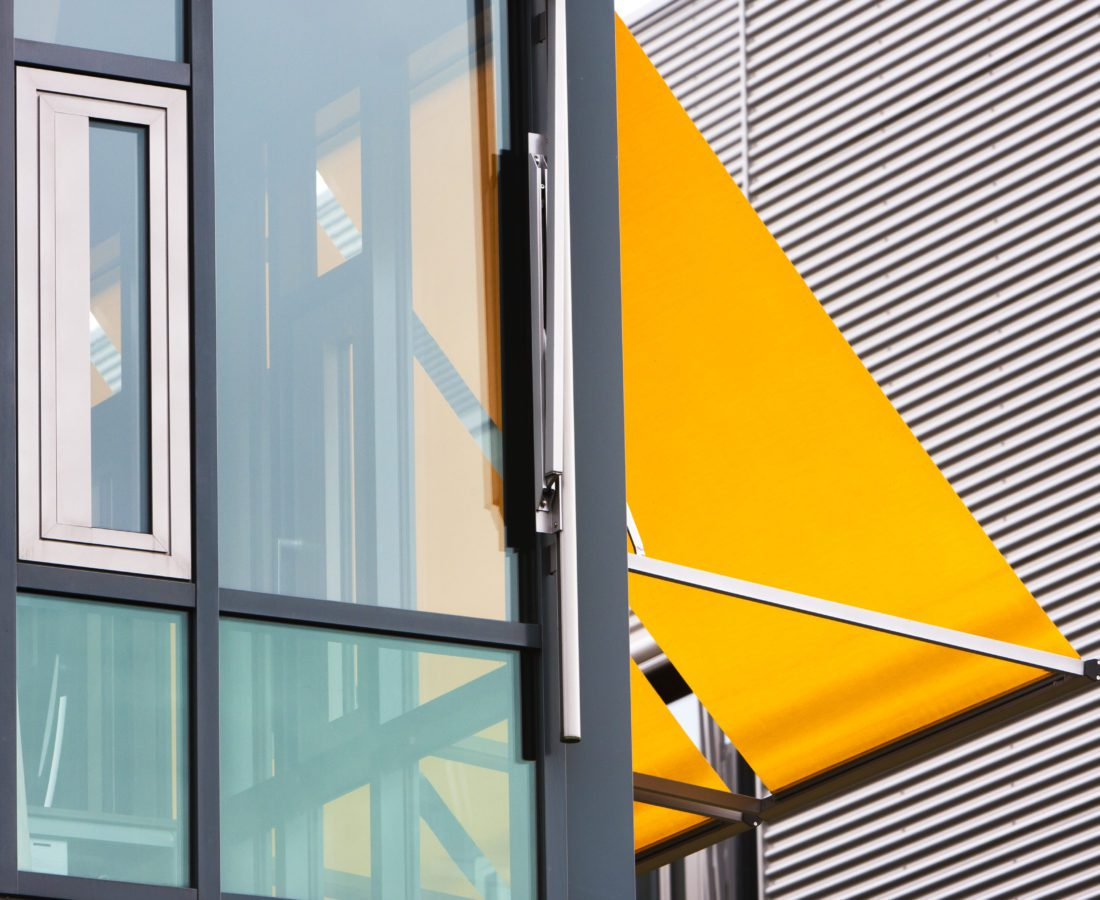 Closeup of a modern office building with yellow awnings