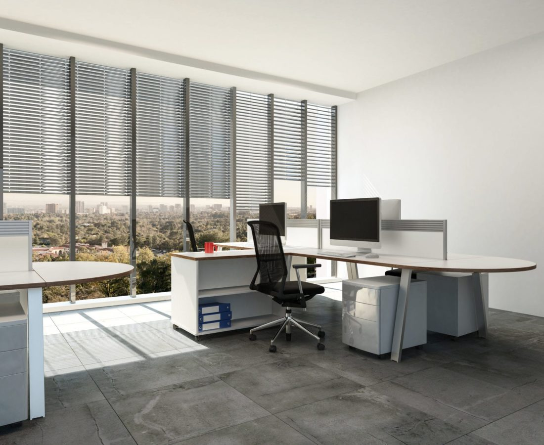 Modern open plan office with large windows and multi seat workstations around table style desks